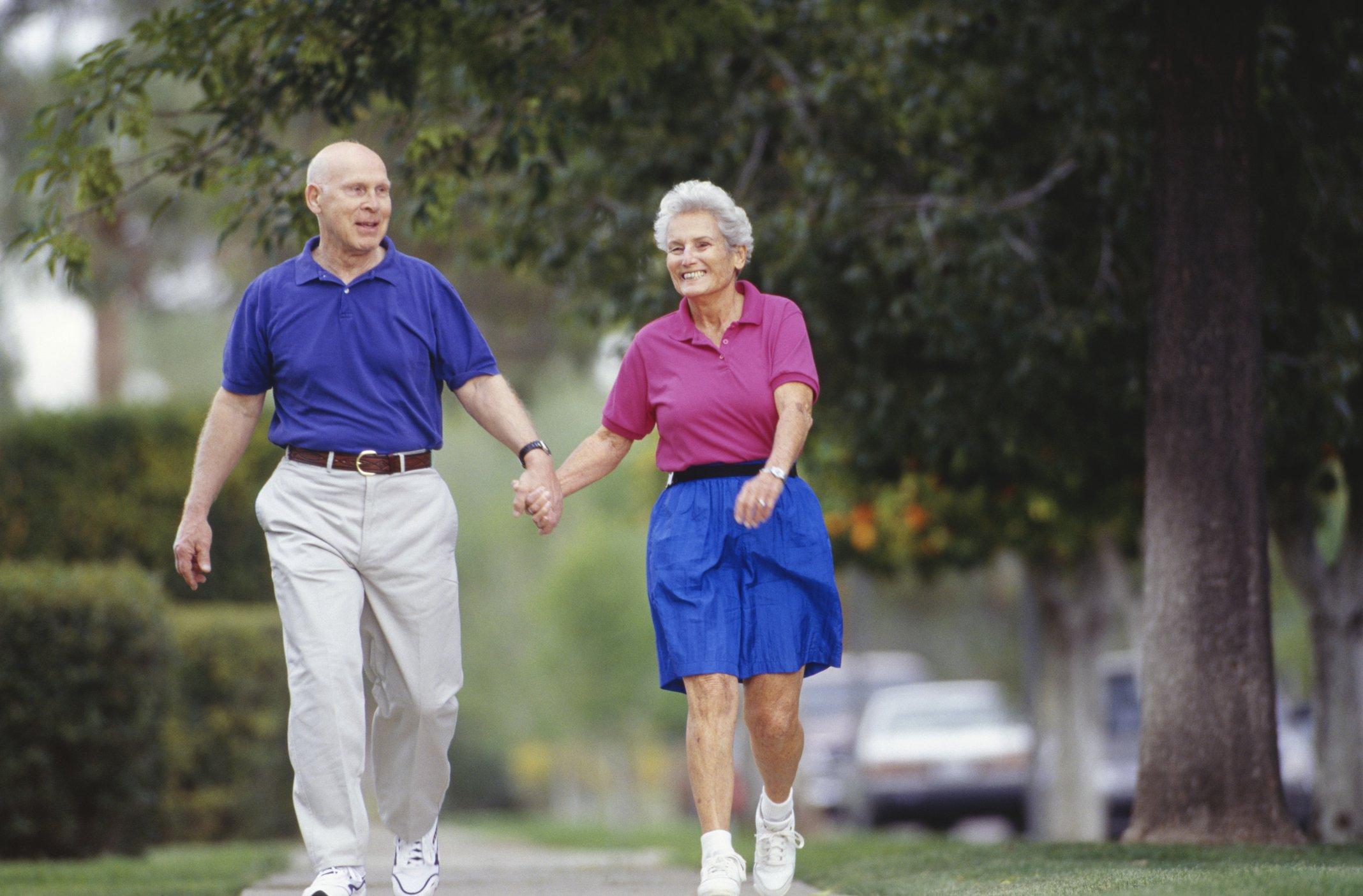 Una pareja mayor caminando por un barrio suburbano