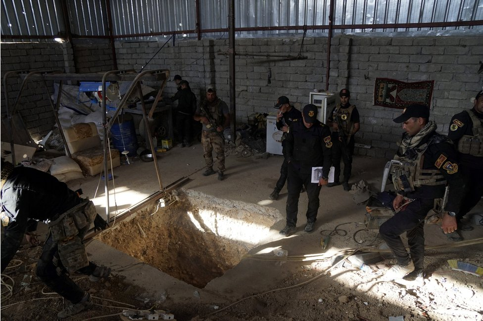 Iraqi security forces stand around a tunnel used by Islamic State militants at Bartila in the east of Mosul on October 20, 2016