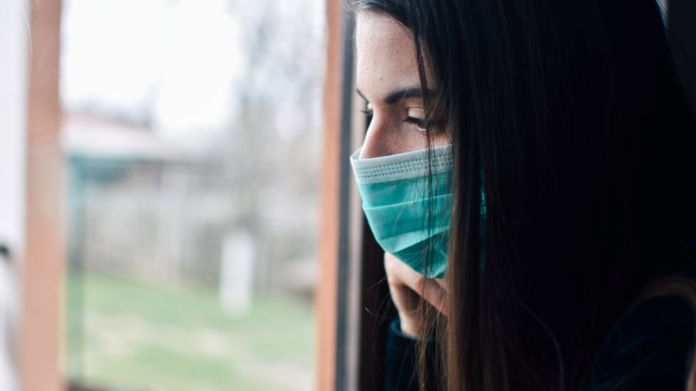 Woman with surgical mask looks out of a window