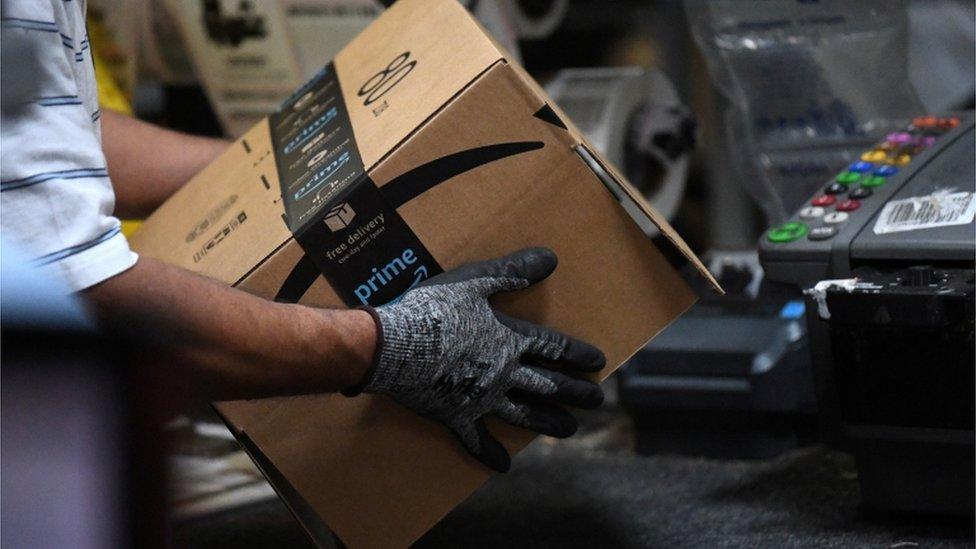 Un trabajador de Amazon prepara una caja para entrega a domicilio.