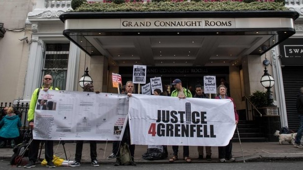 Demonstrators hold placards outside the venue of the inquiry into the Grenfell Tower fire