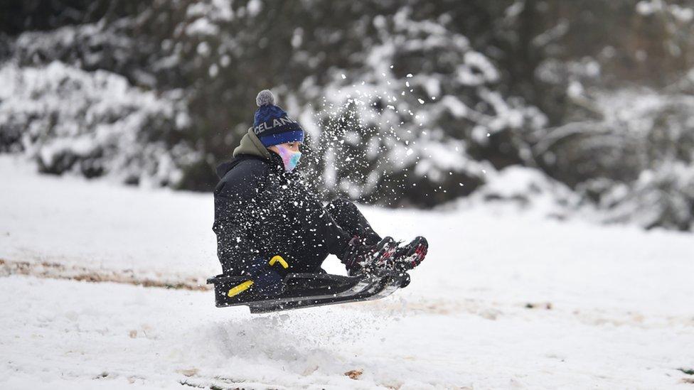 امرأة ترتدي قناعاً وتركب مزلجة أسفل تل في نيوكاسل-أندر-لايم ، ستافوردشر