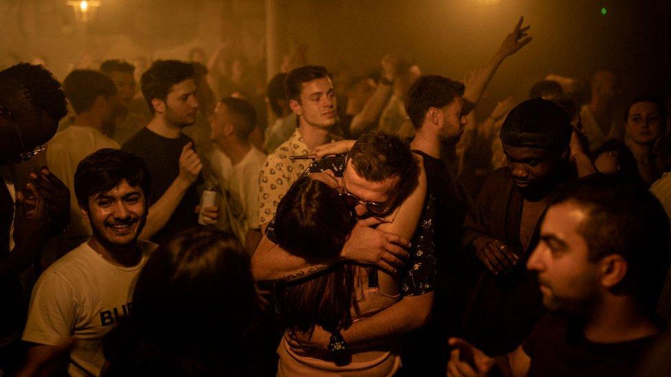 Jóvenes abrazándose en un club nocturno en Londres, Reino Unido.
