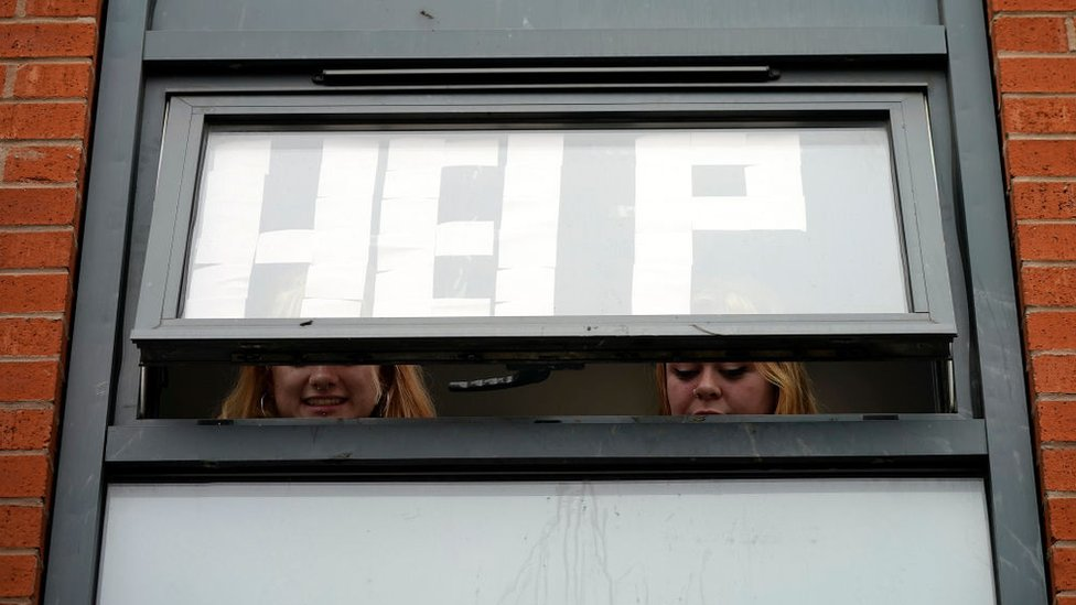 Isolating students peer out of their accommodation window in Manchester