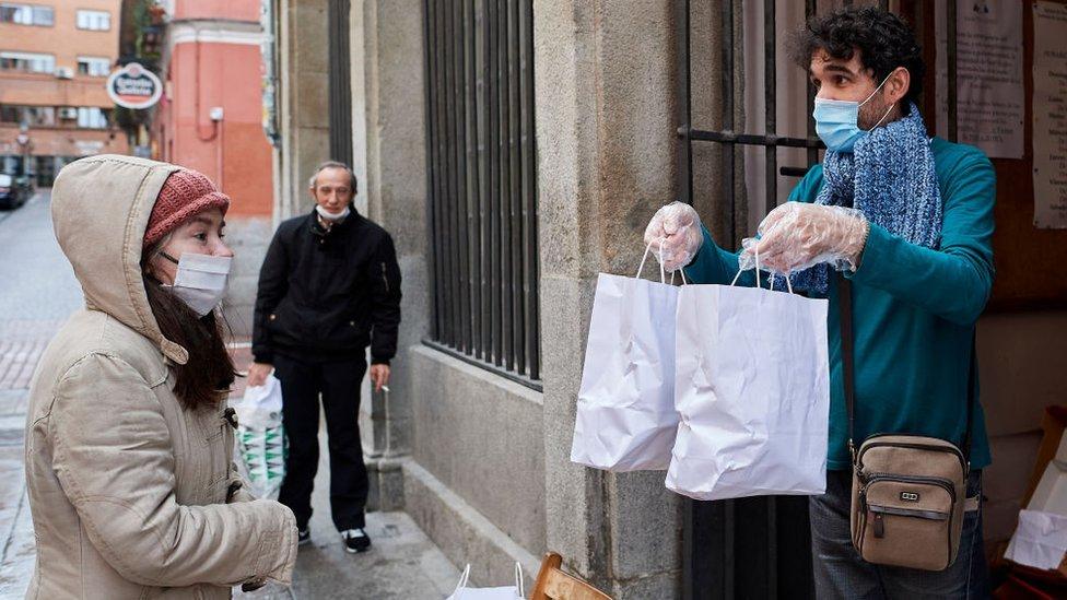 Una mujer recibe unas bolsas con comida en Madrid.
