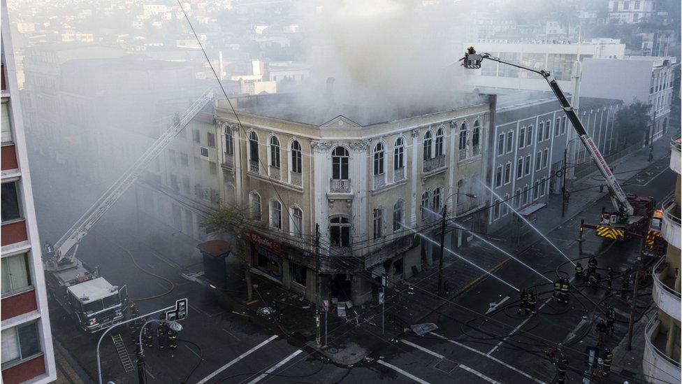 Bomberos tratan de apagar un incendio en una farmacia de Valparaíso.