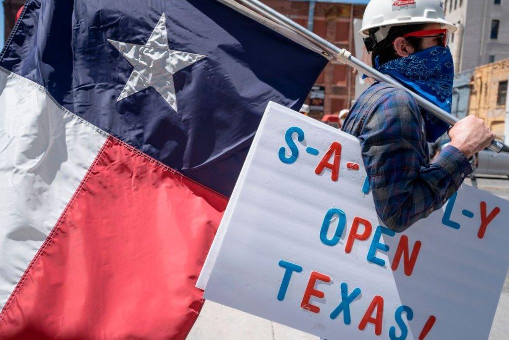 Un hombre lleva una bandera de Texas y un cartel que pide que abran el estado.