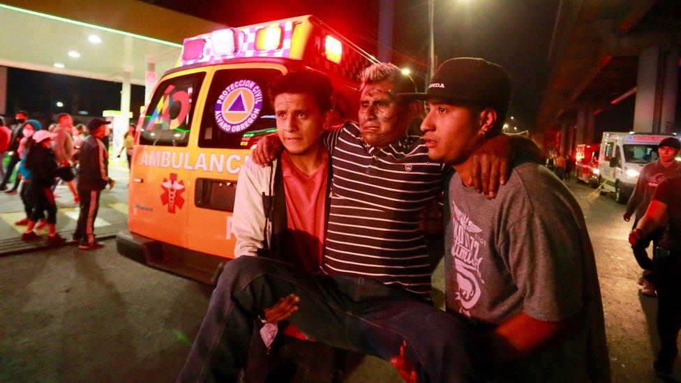 Dos hombres trasladan a un herido en el accidente del metro de Ciudad de México