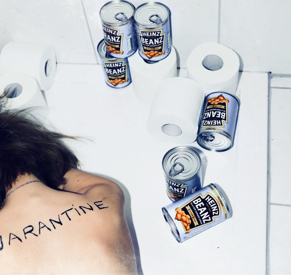 A woman lies in a bath surrounded by cans of baked beans with the word quarantine on her back