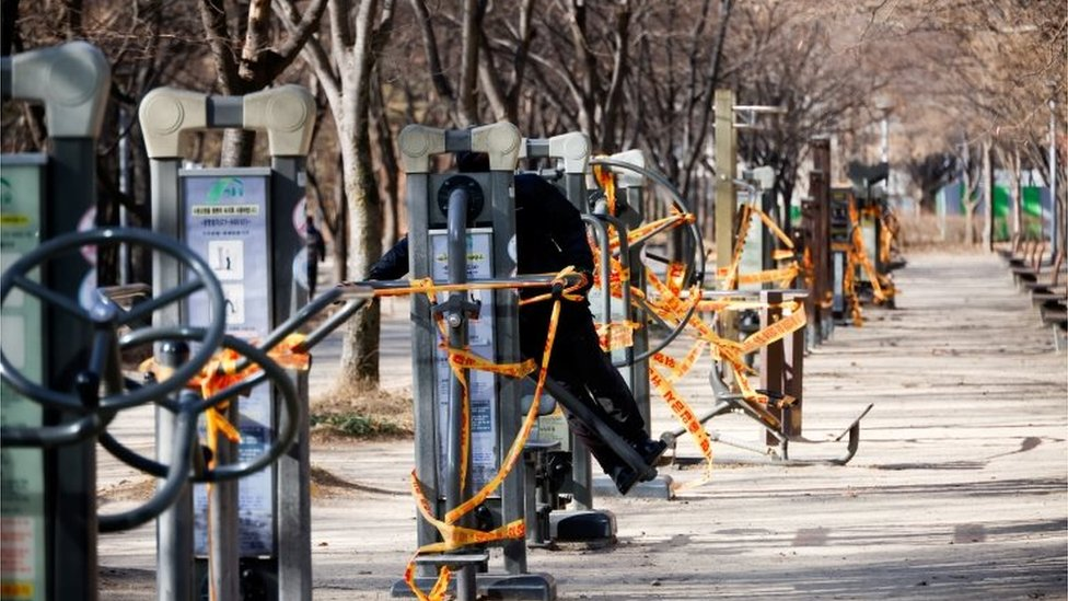 A man tries to use an outdoor gym which has been cordoned off as part of measures to avoid the spread of the coronavirus disease (COVID-19) at a park in Seoul, South Korea, December 30,