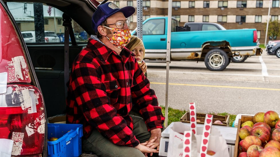 A farmer and his son selling apples from the back of a car