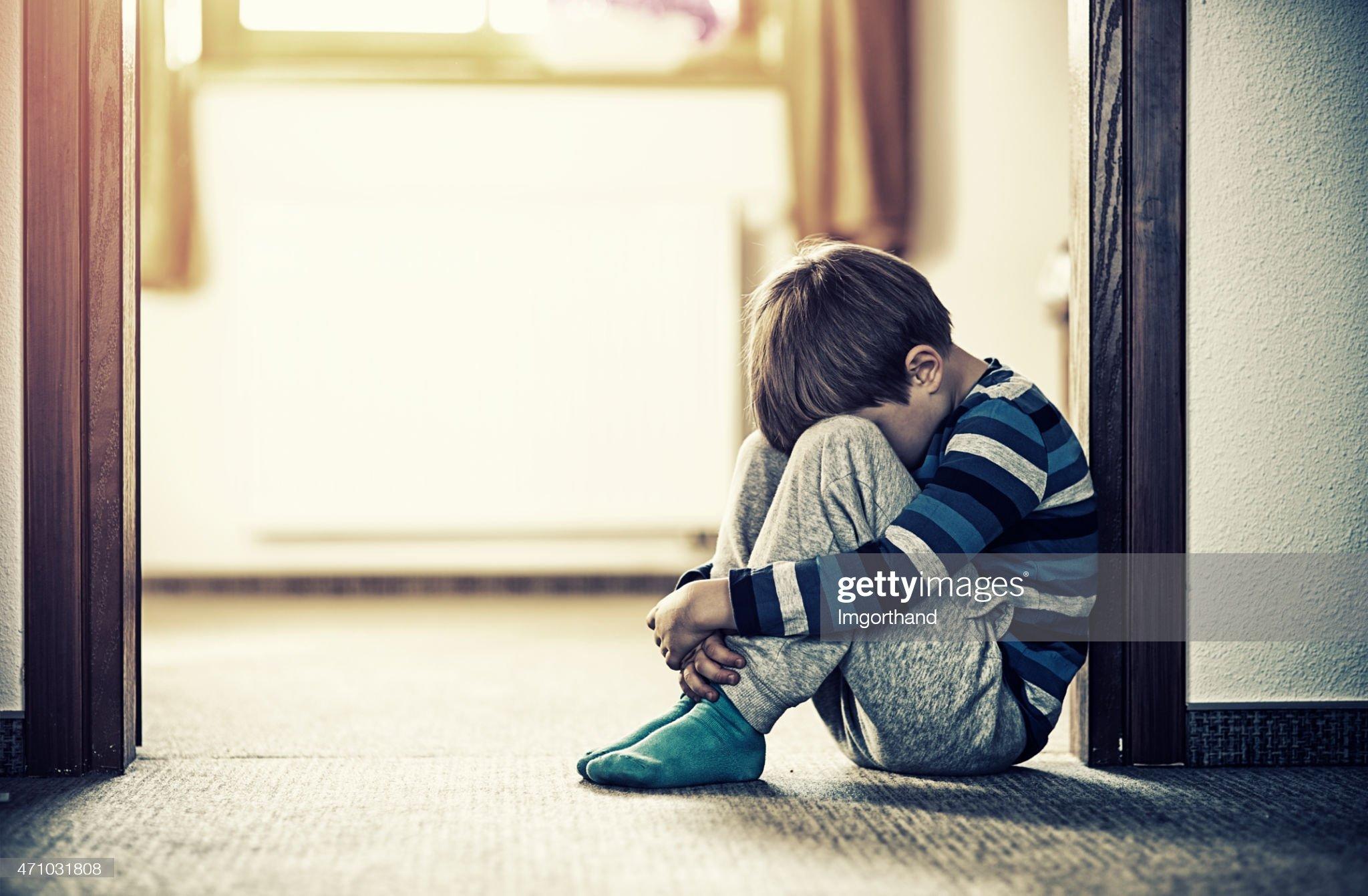 طفل يحلس على الارض ويغطي وجهه