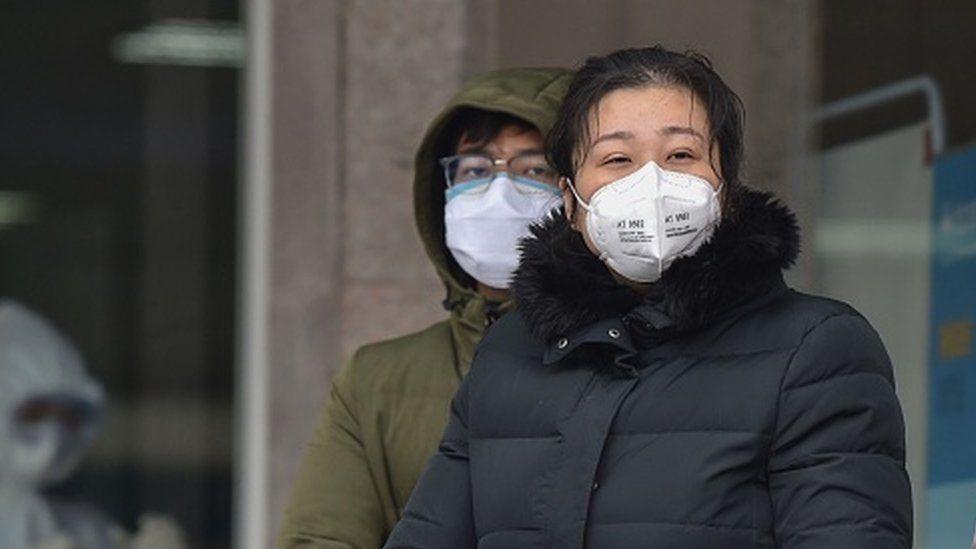 Gente con mascarillas en Wuhan
