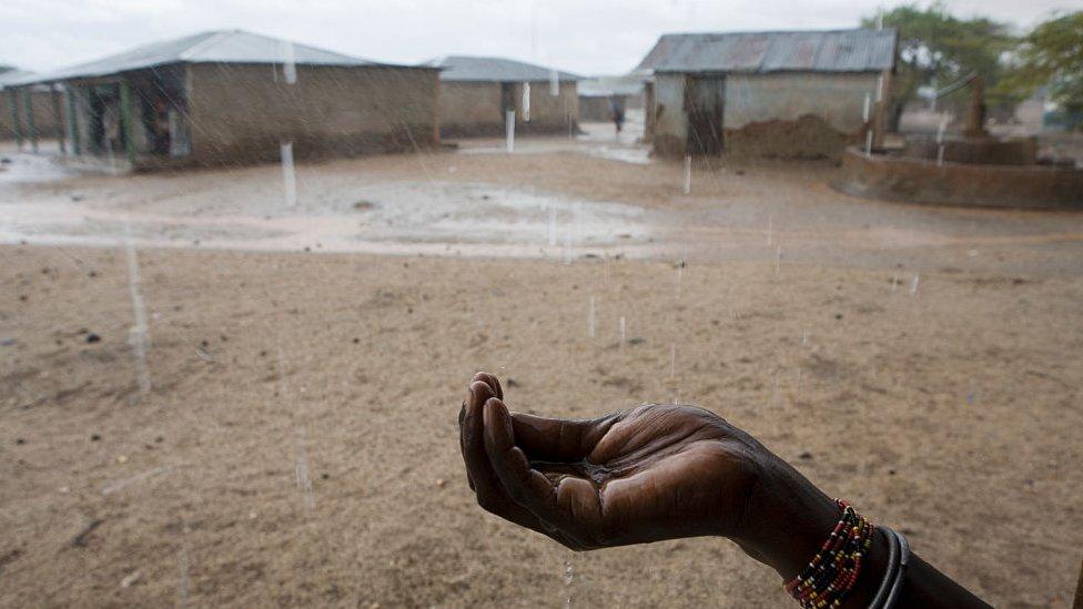 Mujer recoge agua de lluvia en Kenia, África.