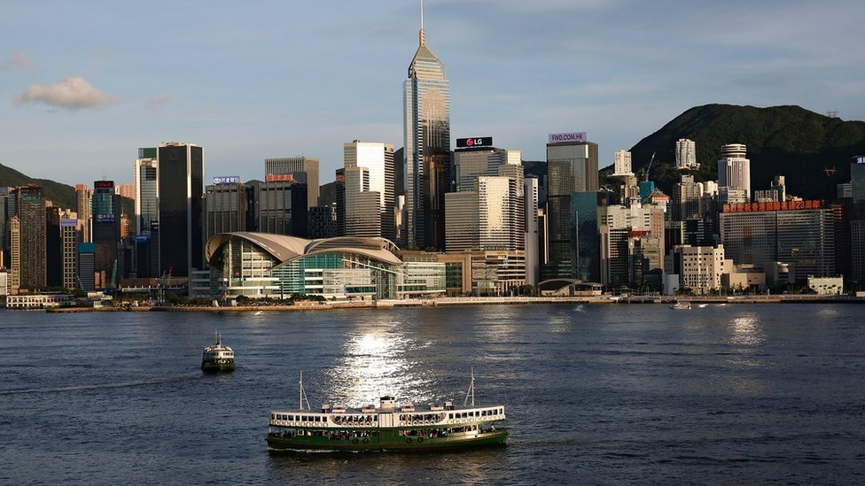 FILE PHOTO: A Star Ferry boat crosses Victoria Harbour in front of a skyline of buildings in Hong Kong, China June 29, 2020
