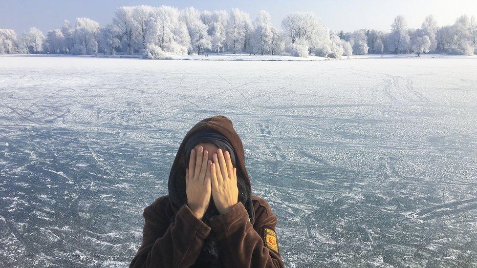 امرأة تحمي وجهها من البرد