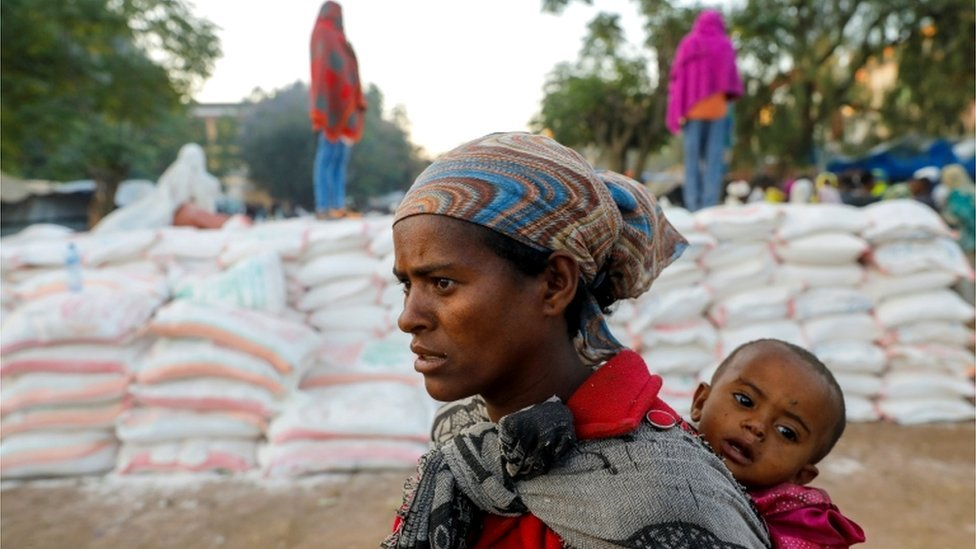 امرأة تحمل رضيعا وهي تقف في طابور للحصول على الطعام، في مدرسة بتغراي