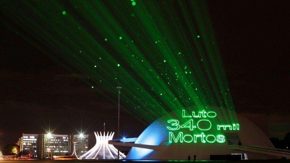 """Projeção nas paredes do museu nacional de Brasília com a mensagem """"Luto 340 mil mortos"""", em referência às pessoas que morreram em decorrência da doença do coronavírus é vista durante um protesto pedindo vacinas e em memória dos mortos, em Brasília, Brasil, 7 de abril de 2021."""