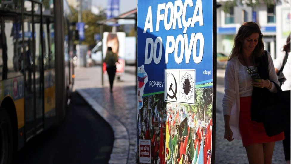 People pass by an election poster of the Portuguese Communist Party and Green Party coalition, in Lisbon Monday, September 2015