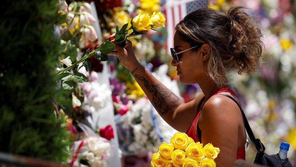 امرأة تضع زهورا في موقع تذكاري لضحايا انهيار البناية
