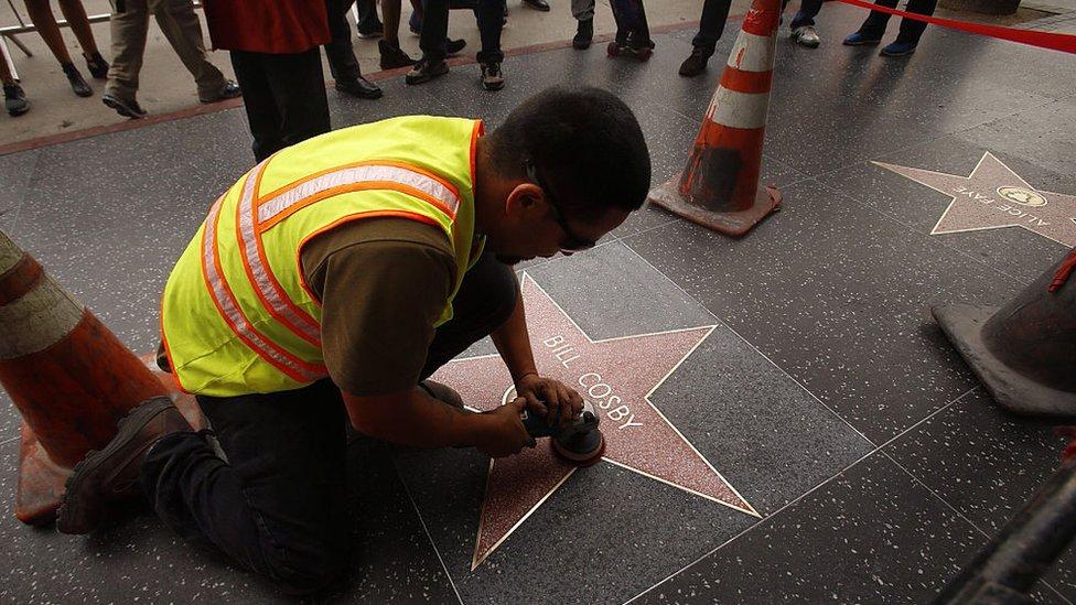 Hombre limpiando estrella de Bill Cosby en el Paseo de la Fama