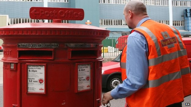 A postal worker emptying a post box in central London,
