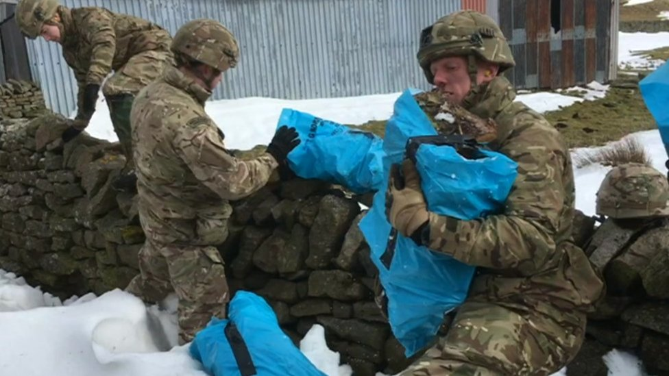 Supplies including logs are carried by Army soldiers at a drop-off near Kirkby Stephen