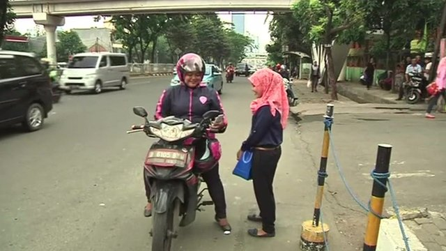 Woman using female-only motorbike service