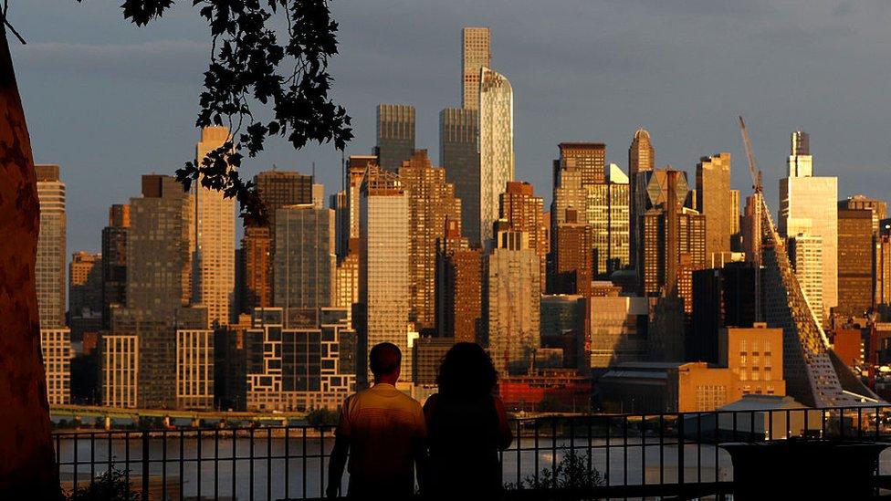 Dos personas frente a unos edificios de Nueva York durante el ocaso.