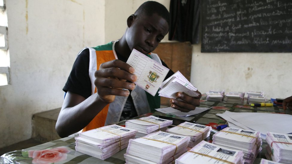 "An Ivory Coast Electoral Commission official holds voting cards during distribution of voting cards ahead of the country""s presidential election that will be held on October 31, 2020 in Abidjan, Ivory Coast, 21 October 2020."