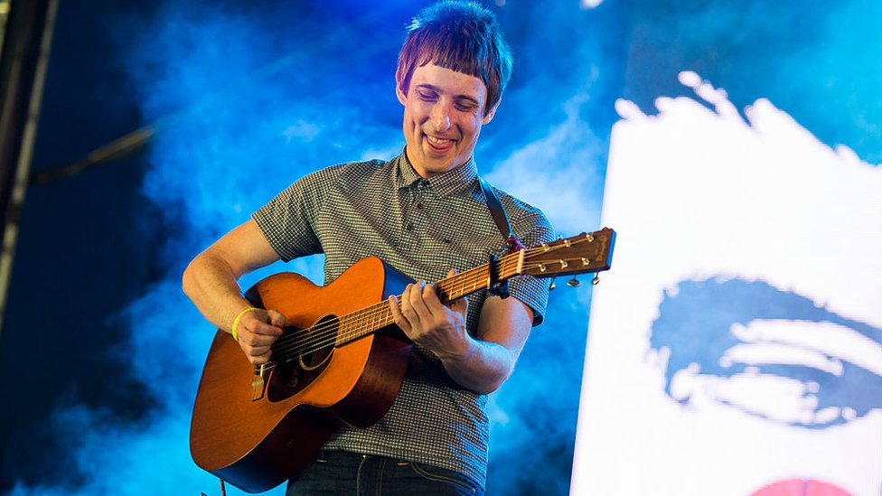 Gerry Cinnamon on stage at T in the Park with an acoustic guitar