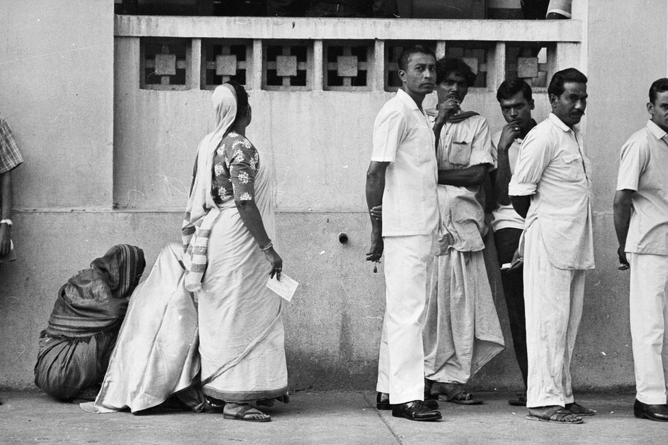 A woman in a queue to vote, turns her face to the wall as men face the camera in 1967