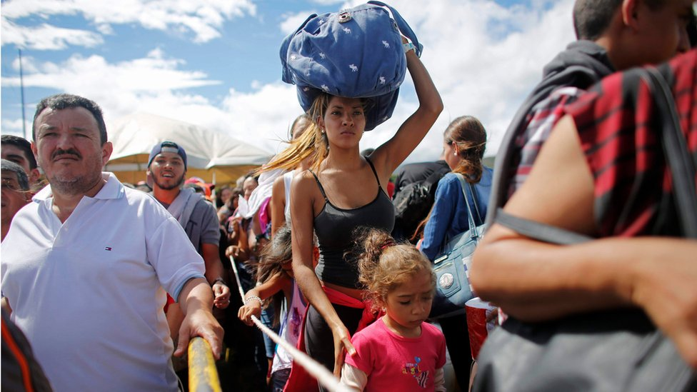 A woman carrying a bundle on her head wait in line to cross the border into Colombia from Venezuela on 17 July