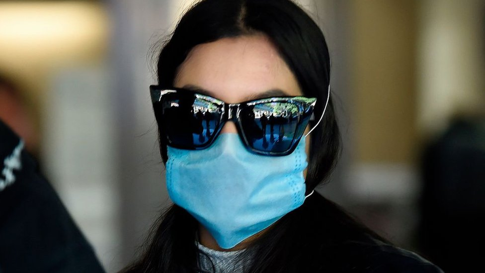 Mujer usando mascarilla y lentes oscuros
