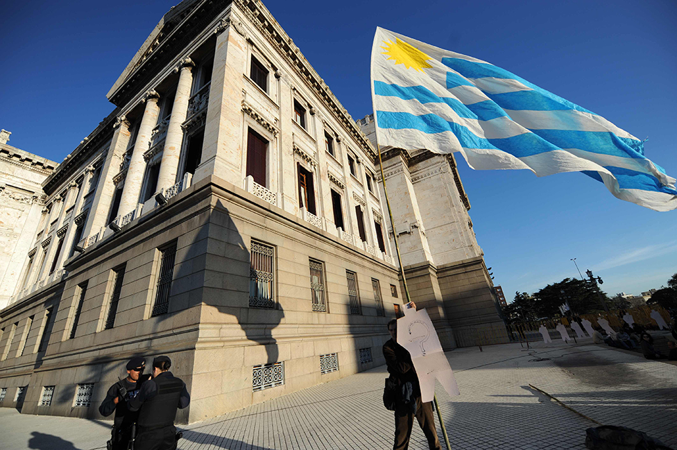Un hombre sostiene una bandera fuera del Parlamento uruguayo en Montevideo.