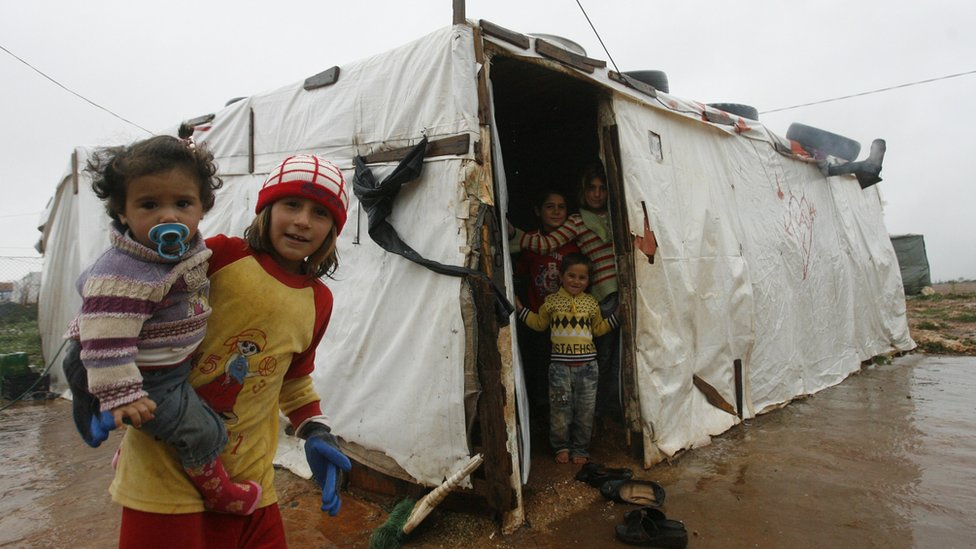 Syrian refugee children stand near their temporary shelter at a refugee camp in Lebanon