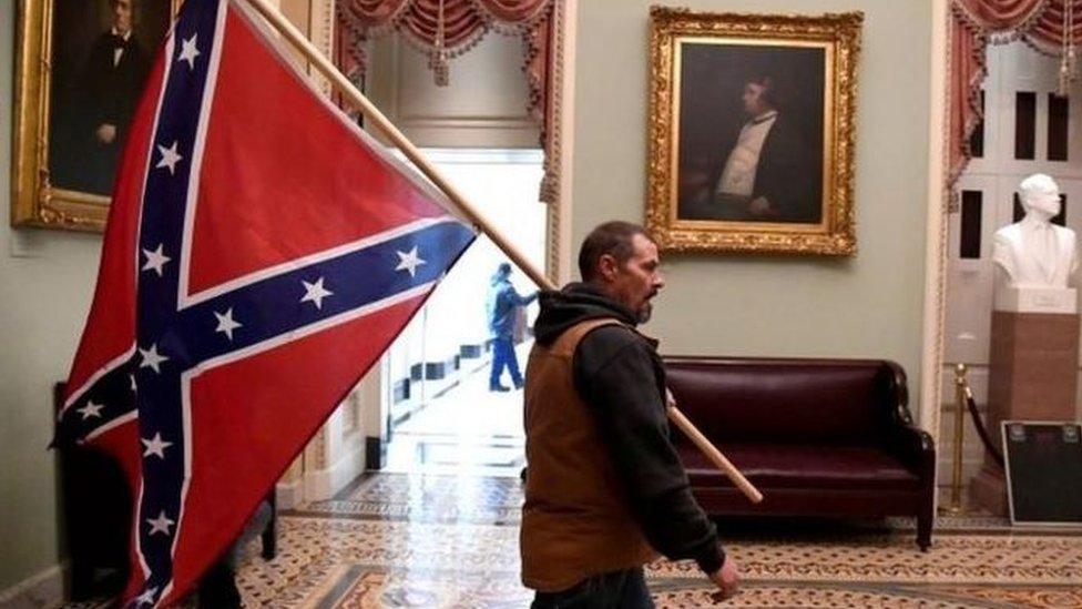 Un simpatizante de Donald Trump entra al Capitolio con una bandera confederada al hombro