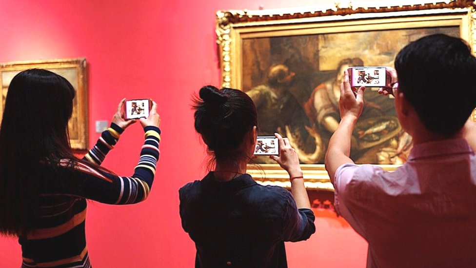 People looking at a painting through smartphone AR app