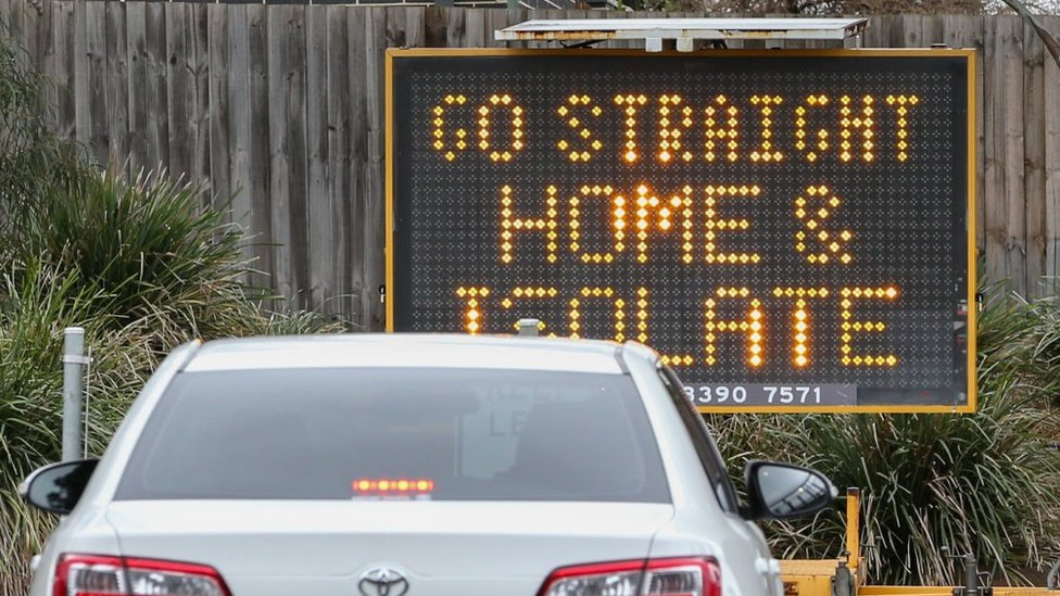 A sign reading 'Go straight home and Isolate' is seen at the exit of a drive through Covid-19 testing site in Melbourne