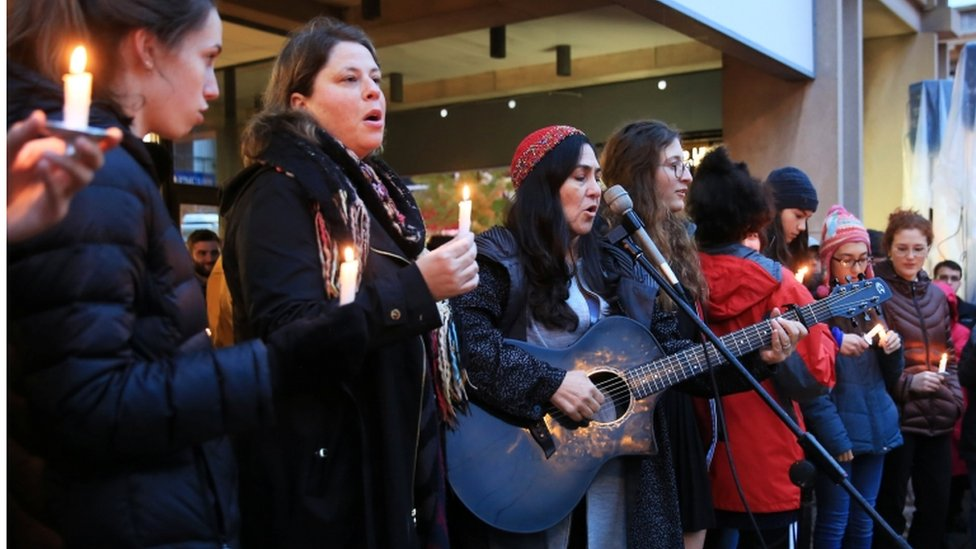 Some of the group, with adults, play music at vigil
