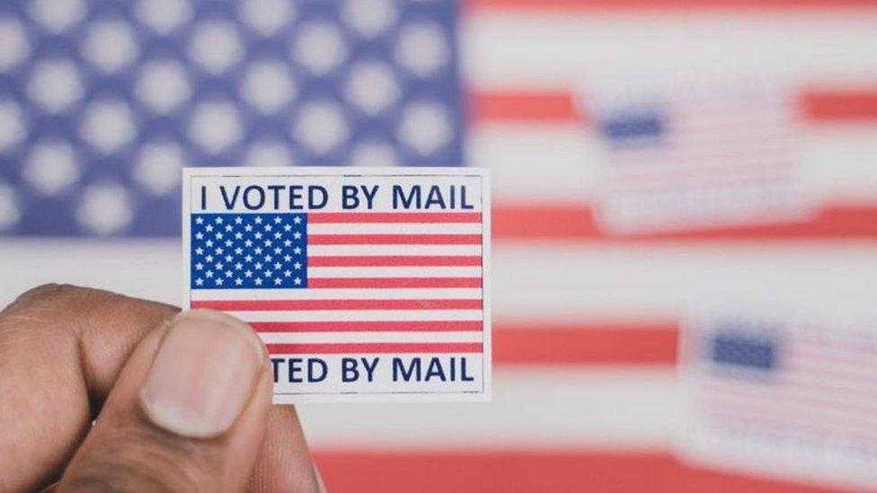 """رجل يحمل ملصق """"لقد قمت بالتصويت عبر البريد"""""""