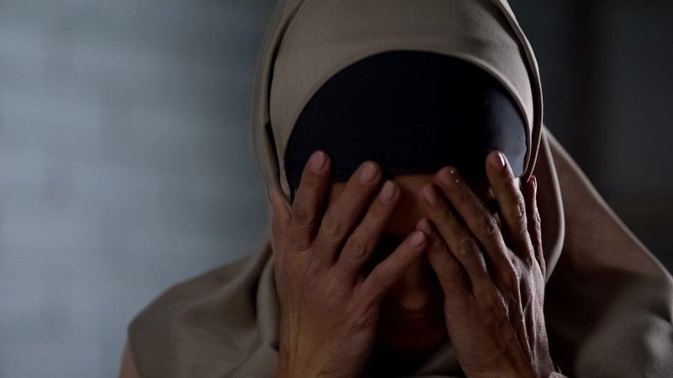 Muslim woman hiding her face