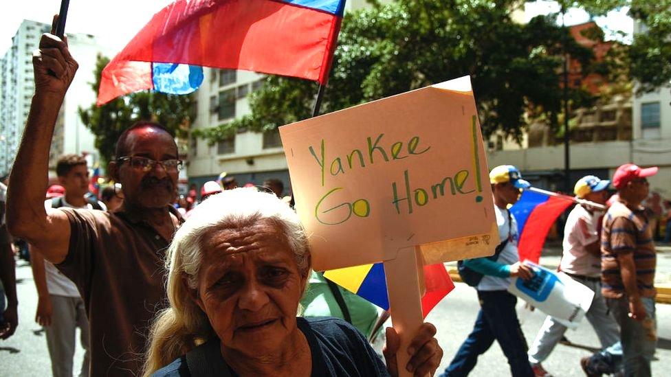 Una mujer en Caracas con una pancarta que dice: Yankee go home!