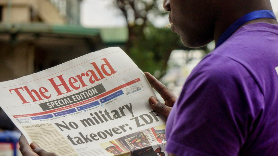 A man reads the front page of a special edition of The Herald newspaper about the crisis in Zimbabwe