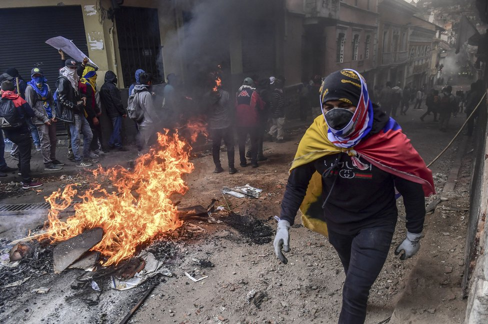 A demonstrator wrapped in an Ecuadorean flag passes by a barricade set on fire during clashes with riot police in Quito, as thousands march against Ecuadorean President Lenin Moreno's decision to slash fuel subsidies, on 9 October 2019.