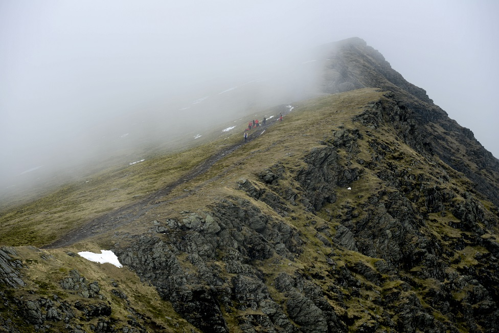 Walkers on a path on a mountain ridge in Britain