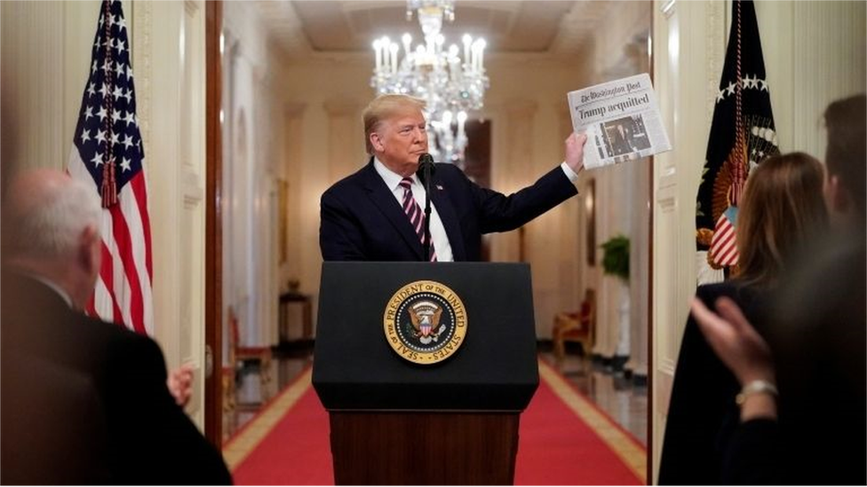 Donald Trump holds up a newspaper announcing his acquittal.