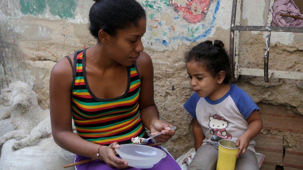 Madre venezolana alimentando a su hija.