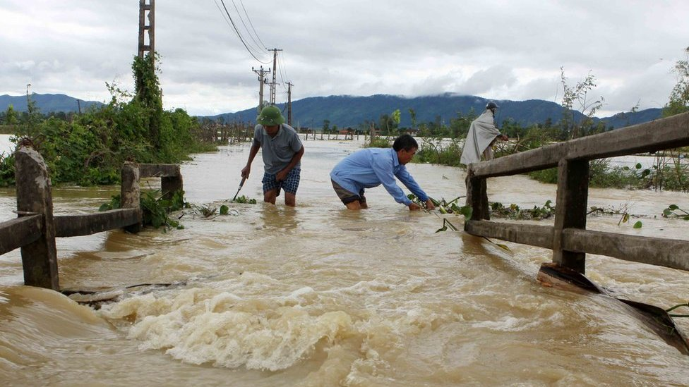 This picture from the Vietnam News Agency taken on 11 October 2017 shows men wading through a flooded area in the central province of Nghe An