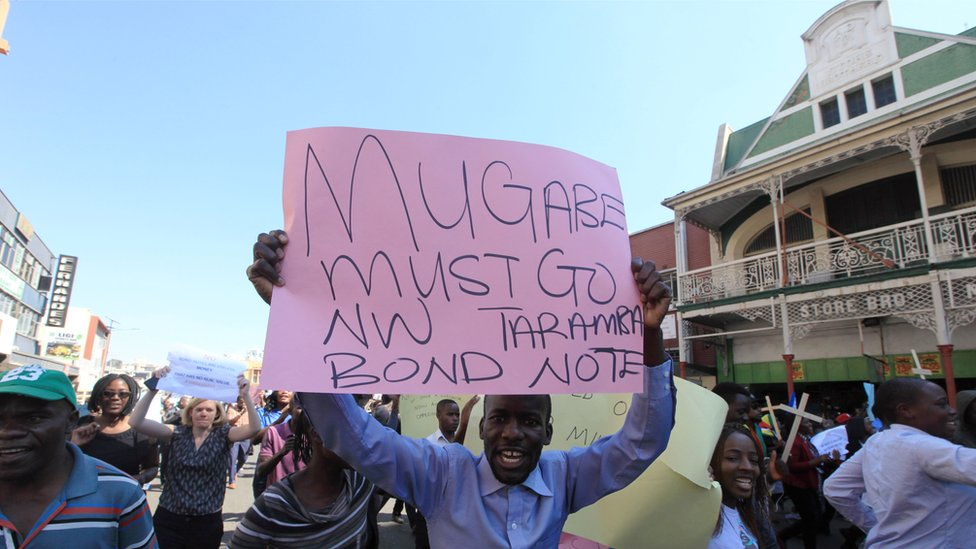 "Protesters in Harare, Zimbabwe, one holding a ""Mugabe must go"" sign - Wednesday 3 August 2016"